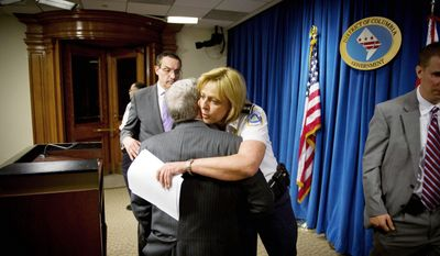 D.C. Police Chief Cathy L. Lanier hugs D.C. Council member Jim Graham of Ward 1 at the end of a press conference Monday to announce an arrest in the March 11 shooting at the International House of Pancakes in Mr. Graham's ward. The case is being investigated as a possible anti-gay hate crime. (Rod Lamkey Jr./The Washington Times)