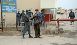 An Afghan policeman checks a man entering a provincial police station near the main gate of a joint civilian-military base where two British soldiers were killed in Lashkar Gah in Afghanistan's Helmand province on Monday, March 26, 2012. (AP Photo/Abdul Khaleq)