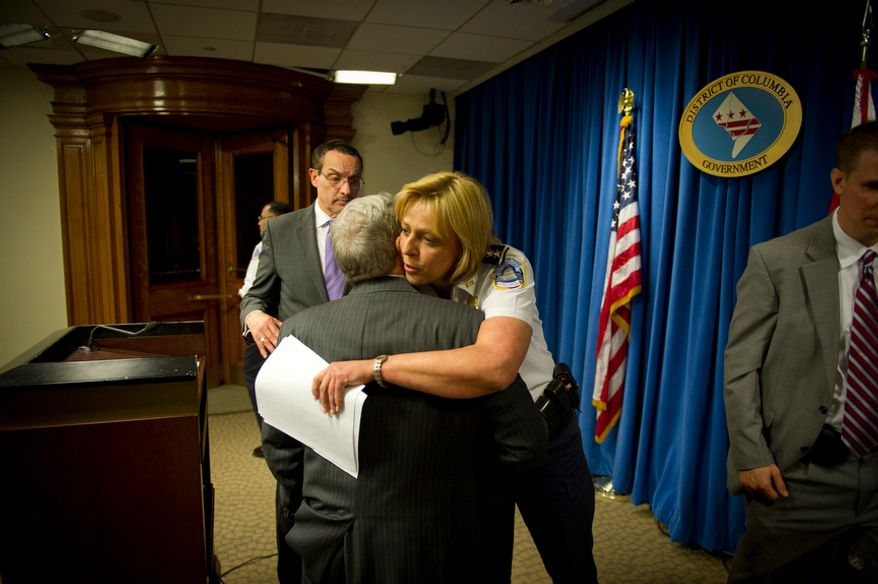 D.C. Mayor Vincent C. Gray (left) exits as Metropolitan Police Chief Cathy L. Lanier hugs D.C. Council member Jim Graham, Ward 1 Democrat, after a March 26, 2012, press conference at the John A. Wilson Building in D.C., to announce an arrest in a March 11 anti-LGBT shooting at a IHOP restaurant in the city's Columbia Heights neighborhood. (Rod Lamkey Jr./The Washington Times)