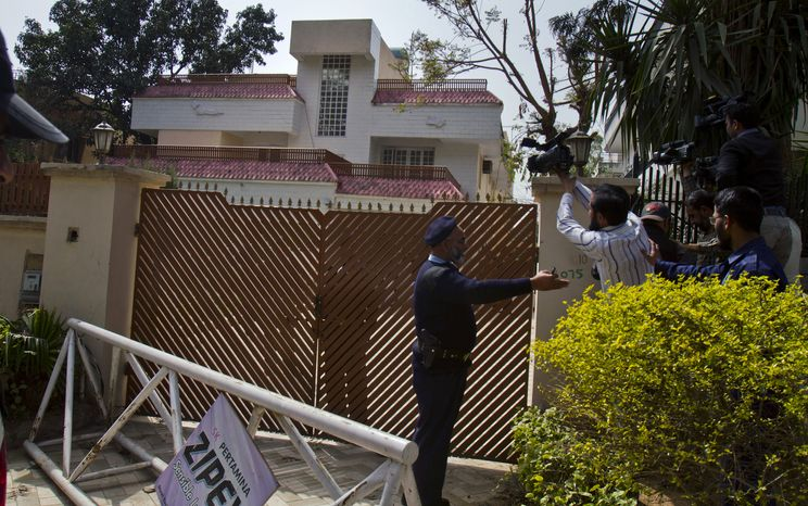 Pakistani police officers stop cameramen from filming a house where family members of slain al Qaeda leader Osama bin Laden are believed to be held on Saturday, March 17, 2012, in Islamabad. (AP Photo/An