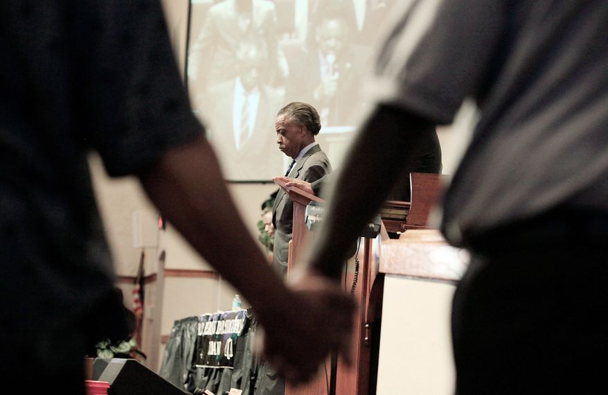 The Rev. Al Sharpton joins others in a prayer led by the Rev. Jesse Jackson at a community forum held Monday at Macedonia Baptist Church in Eatonville, Fla., in connection with the Trayvon Martin case. (Associated Press)