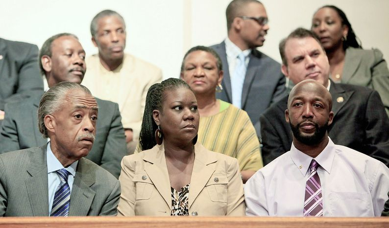 Sybrina Fulton and Tracy Martin, the parents of Trayvon Martin, sit with the Rev. Al Sharpton (left)