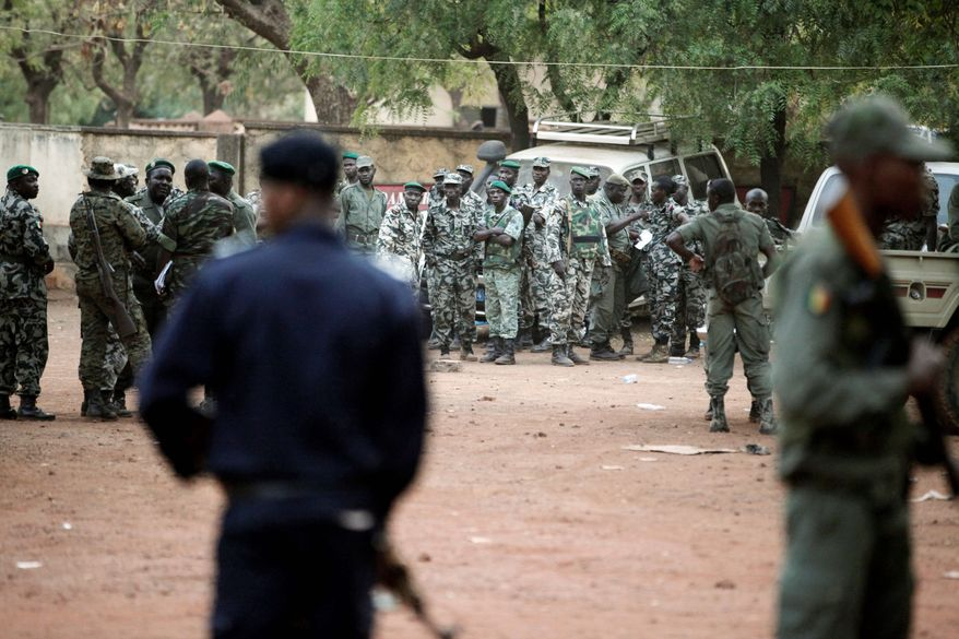 Soldiers stand guard Tuesday outside the headquarters of coup leader Capt. Amadou Haya Sanogo at a military base near Bamako, Mali. Already, the U.S., the European Union and France have cut off aid. Additional sanctions from the region would be a further blow to the junta.