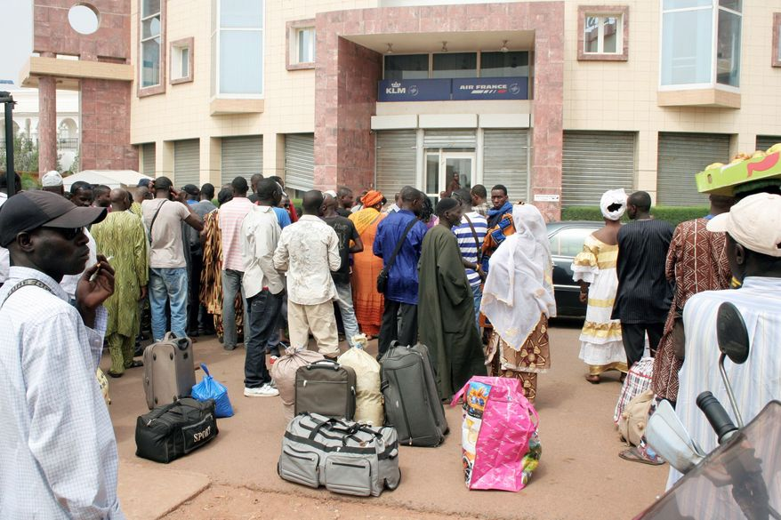 ASSOCIATED PRESS PHOTOGRAPHS People in Mali wait outside a travel agency Tuesday to buy tickets. The country's airport reopened almost a week after a military coup. The body representing nations in western Africa suspended Mali and put a peacekeeping force on standby.
