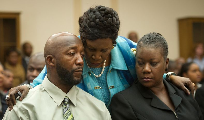 Rep. Sheila Jackson Lee (center), Texas Democrat, offers words to Tracy Martin (left) and Sybrina Fulton, parents of slain teen Trayvon Martin, as they appear March 27, 2012, at a House briefing at the Rayburn House Office Building on Capitol Hill. (Rod Lamkey Jr./The Washington Times)