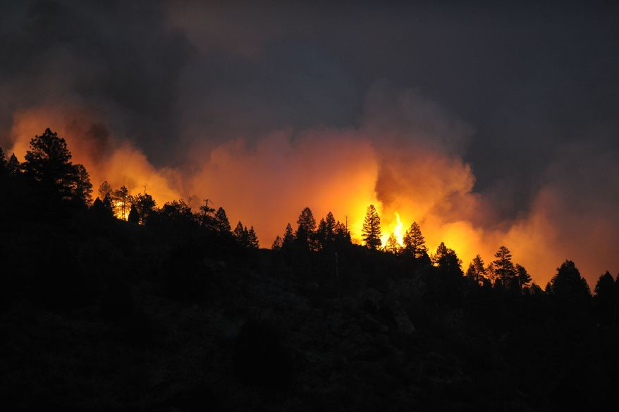 A fast-moving wildfire tops out trees as the blaze just about comes over the ridge on Monday, March 26, 2012, near Reynolds Ranch in Conifer, Colo. (AP Photo/Denver Post, John Leyba)