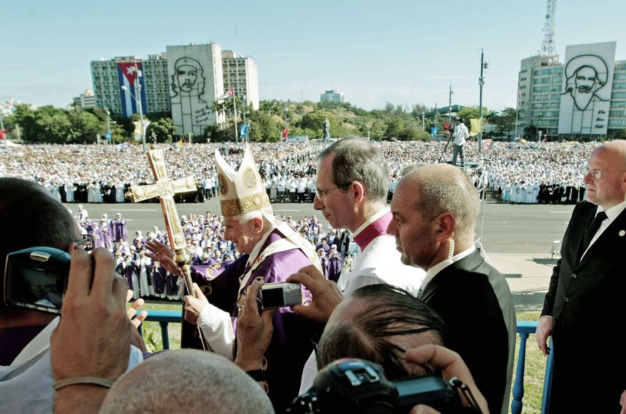 "Pope Benedict XVI arrives to lead an open-air Mass at Revolution Square in Havana on Wednesday, his last day in Cuba. The square includes an image of Communist hero Ernesto ""Che"" Guevara (background, left). (Associated Press)"