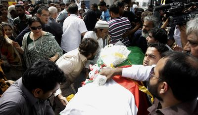 People carry the body of a Pakistani acid attack victim Fakhra Younnus, at Karachi airport in Pakistan Sunday, March 25, 2012. Fakhra who committed suicide by jumping from the sixth floor of her flat in Rome, was a victim of an acid attack allegedly carried out 12 years ago by her husband. (AP Photo)