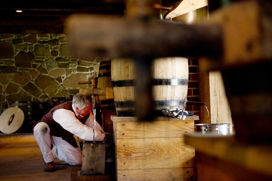 Tim Larner, a Historic Trades Interpreter with Mount Vernon, adds wood to the fire at George Washington's reconstructed distillery.  (Andrew Harnik/The Washington Times)