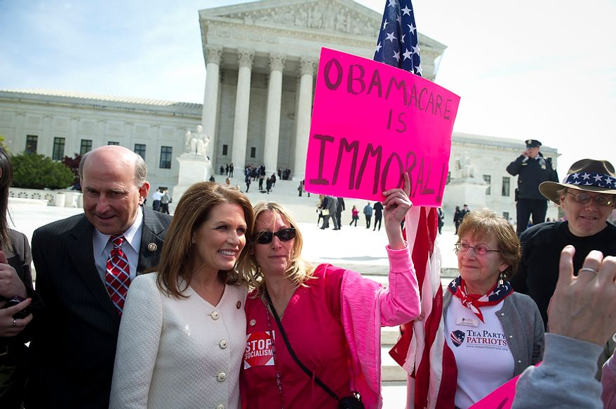 Former Presidential candidate Rep. Michele Bachmann (R-Minn) poses for a photo with Lisa Nancollas of Lewistown, Pa., as Rep. Louie Gohmert (R-Tex) stands at left as they wait to speak to a crowd during a Tea Party Patriots rally in front of the Supreme Court of the United States in Washington, D.C., Wednesday, March 28, 2012, as the nation's high court takes up arguments regarding President Obama's health care overhaul. (Rod Lamkey Jr/The Washington Times)