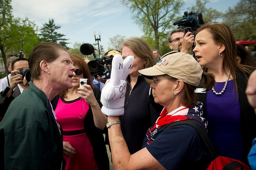 A man who refused to be identified (left) shouts out at Janis Haddon (center) of Atlanta, Ga., and Tea Party Patriots Co-Founder Jenny Beth Martin (right) of Atlanta, Ga., in front of the Supreme Court of the United States in Washington, D.C., Wednesday, March 28, 2012, as the nation's high court takes up arguments regarding President Obama's health care overhaul. (Rod Lamkey Jr/The Washington Times)
