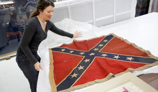 ** FILE ** In this Feb. 24, 2012, photo, Cathy Wright, curator at the Museum of the Confederacy in downtown Richmond, opens an original battle flag from the 3rd Virginia Infantry. The museum is opening a satellite museum Saturday in Appomattox, the first in a regional system of museums. (AP Photo/Richmond Times-Dispatch, Dean Hoffmeyer)
