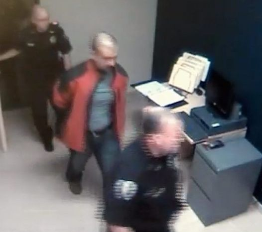 ** FILE ** George Zimmerman is escorted into the Sanford, Fla., police station in handcuffs the night he fatally shot Trayvon Martin. (Associated Press)