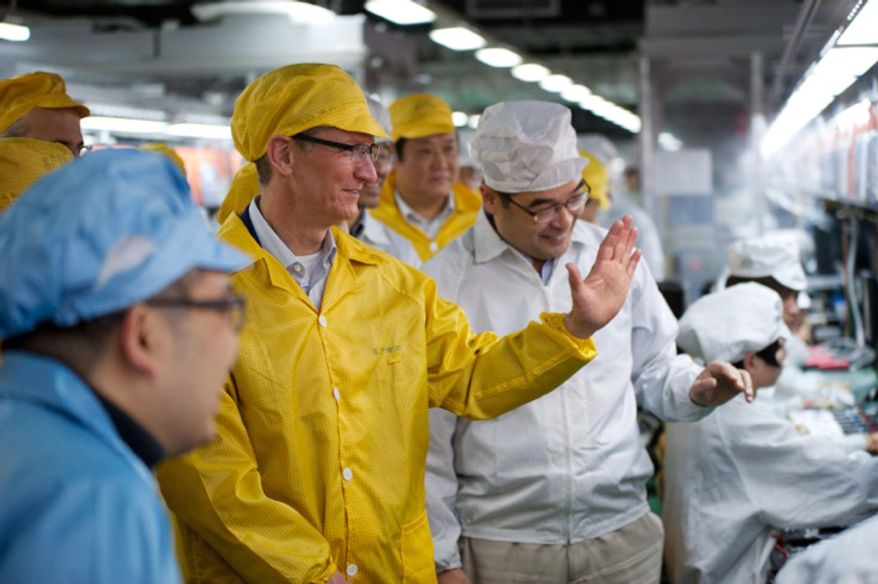 In this March 28, 2012 photo provided by Apple, Inc., Apple CEO Tim Cook (center) visits the iPhone production line at the newly-built manufacturing facility Foxconn Zhengzhou Technology Park, which employs 120,000 people. (Associated Press/Apple)