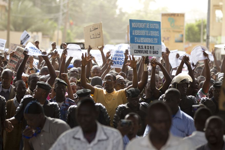 Demonstrators march along a central street in Bamako, Mali, on Wednesday, March 28, 2012, as thousands rallied in a show of support for the recent military coup. (AP Photo/Rebecca Blackwell)