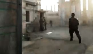 This image made from amateur video and released by Shaam News Network on Tuesday, March 27, 2012, purports to show a Syrian running to help a wounded man in Homs, Syria. (AP Photo/Shaam News Network via APTN)