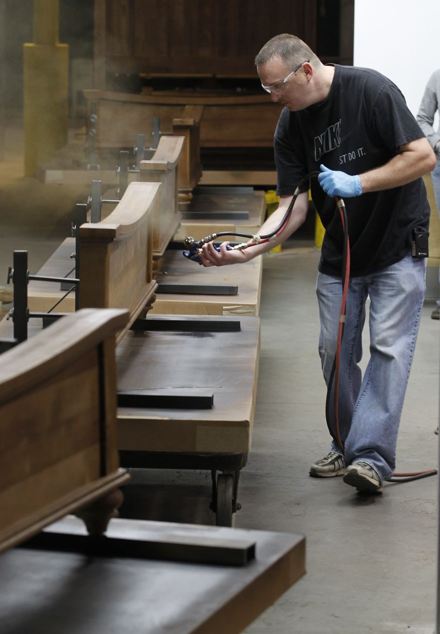 Mark Bollinger sprays a finish on some wooden footboards for beds inside a spray booth at the Lincolnton Furniture Company in Lincolnton, N.C., on March 16, 2012. (Associated Press)