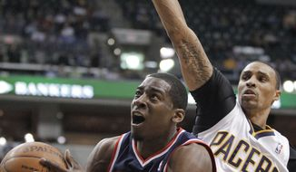 Washington Wizards' Jordan Crawford puts up a shot against Indiana Pacers' George Hill during the first half Thursday, March 29, 2012, in Indianapolis. (AP Photo/Darron Cummings)