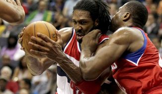 Washington Wizards center Nene drives through Philadelphia 76ers power forward Elton Brand in the second half, Friday, March 30, 2012, in Washington. The Wizards won 97-76. (AP Photo/Carolyn Kaster)
