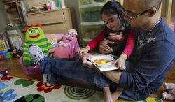 ** FILE ** Christopher Astacio reads with his daughter Cristina, 2, who recently was diagnosed with a mild form of autism, in her bedroom on Wednesday, March 28, 2012, in New York. Autism cases are on the rise again, largely because of wider screening and better diagnosis, federal health officials say. (AP Photo/Bebeto Matthews)
