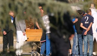 Relatives react by the coffin of Mohamed Merah during his funeral ceremony near Toulouse, France, on March 29, 2012. Mohamed Merah is blamed for a series of deadly shootings which have shocked France and upended the country's presidential race. (Associated Press)