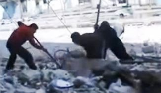 This image made from amateur video on March 23, 2012, purports to show Syrians pulling out the body of a man under the rubble of a building that was bombed in Homs, Syria. (Associated Press/Syria Media Center via APTN)