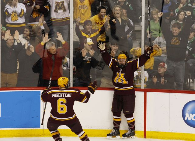 Minnesota's Travis Boyd, right, celebrates with Jake Parenteau (6) after scoring on North Dakota goalie Aaron Dell during the second period of the NCAA men's college hockey tournament West Regional final, Sunday, March 25, 2012, in St. Paul, Minn. (AP Photo/Genevieve Ross)