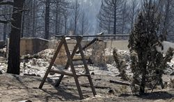The ruins of a home destroyed by a wildfire are framed by a child's swing set near Conifer, Colo., on March 28, 2012. Two people died in the wildfire that started two days earlier. (Associated Press)