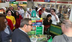Kinju Patel and her husband, Kinjal Patel, owners of the 7-11 store in Northfield, N.J., sell lottery tickets for Mega Millions as a line forms in the store Friday, March 30, 2012. (AP Photo/The Press of Atlantic City, Vernon Ogrodnek)
