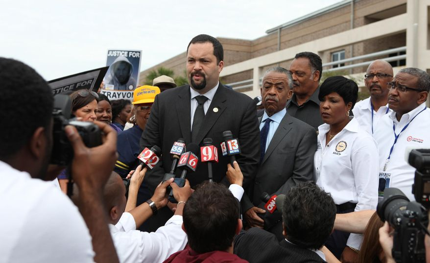 Benjamin Jealous, president of the NAACP, talks to the media as the Rev. Al Sharpton and the Rev. Jessie Jackson, back, listens before the march and rally for slain Florida teenager Trayvon Martin on Saturday, March 31, 2012, in Sanford, Fla. (AP Photo/Julie Fletcher)