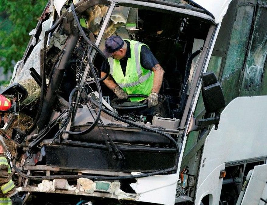 An emergency worker wrestles with the steering wheel on a wrecked bus in which 17 passengers headed for a retreat in Missouri died Aug. 8, 2008, in Sherman, Texas. The bus had been inspected at a state-certified station, an operation that many safety advocates believe receives lax federal oversight. (Associated Press)