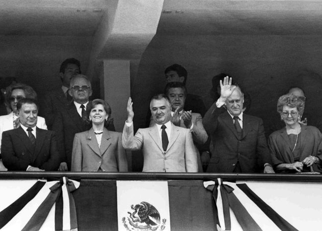 ** FILE ** Then Mexican President Miguel de la Madrid (center) waves to the crowd after the opening ceremony of the World Cup soccer tournament in Mexico City on May 31, 1986. (AP Photo, File)