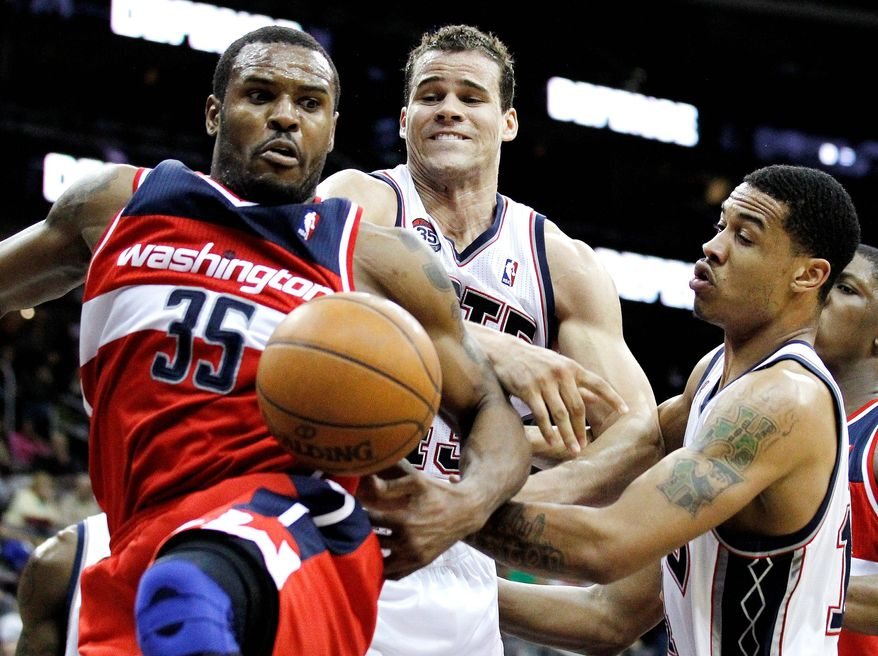 Washington's Trevor Booker (left), shown against New Jersey on March 21, is in a walking boot, the result of an injury suffered in Friday night's win over Philadelphia. (Associated Press)