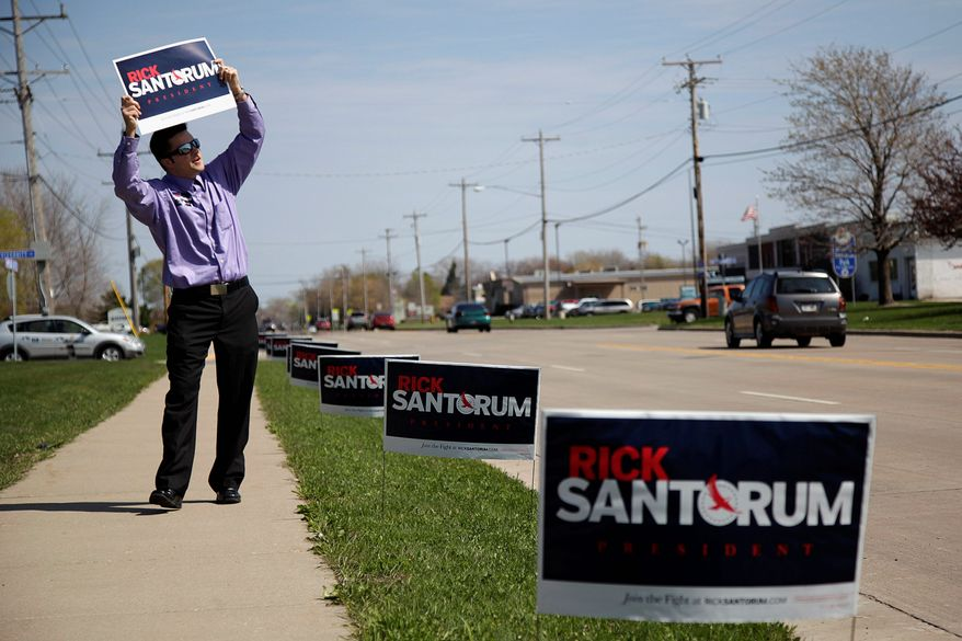 "Corey Essler, a volunteer for former Sen. Rick Santorum of Pennsylvania, a Republican presidential candidate, holds up a sign to woo voters in Menasha, Wis., on Monday. ""You have the opportunity to shock the world,"" Mr. Santorum said. (Associated Press)"