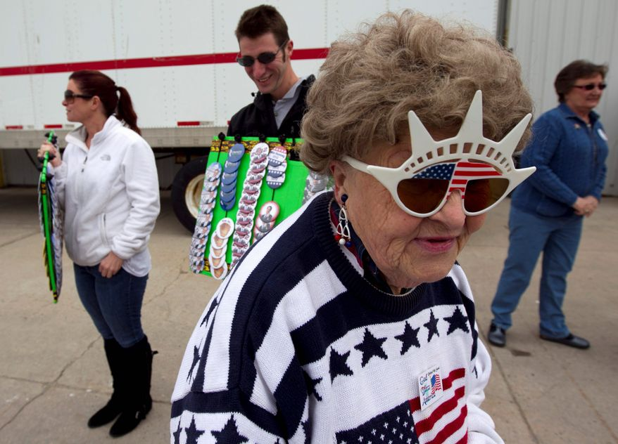 Elsbeth Knutson of Green Bay, Wis., a Romney supporter, wears American-flag glasses before the start of a Romney campaign event at a building supply store in Green Bay on Monday. Mr. Romney ignored his primary rivals Monday and took aim at President Obama. (Associated Press)