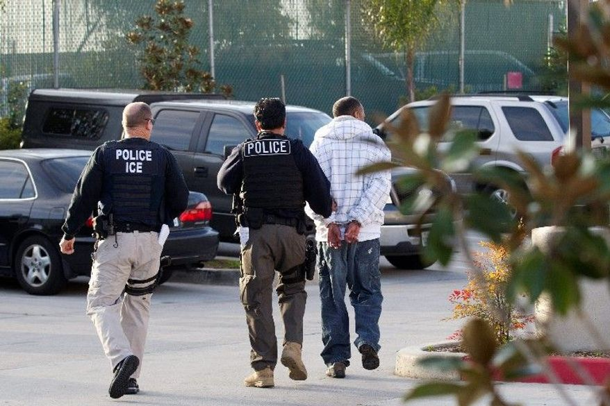 **FILE** Immigration and Customs Enforcement (ICE) agents take a suspect into custody as part of a nationwide immigration sweep in Chula Vista, Calif., on March 30, 2012. (Associated Press)