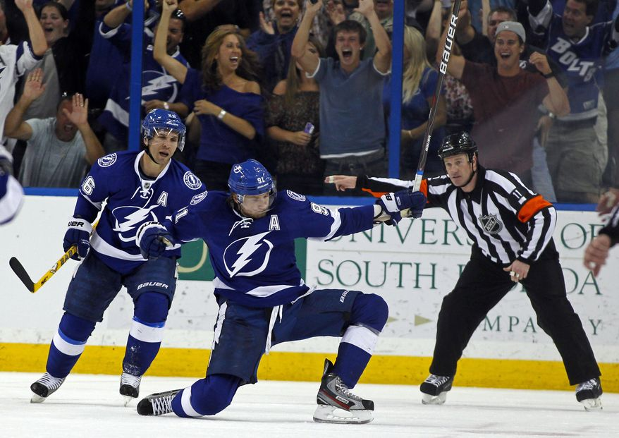 Tampa Bay Lightning's Steven Stamkos celebrates his goal as referee Kelly Sutherland signals against the Washington Capitals on Monday, April 2, 2012, in Tampa, Fla. The Lightning won 4-2. (AP Photo/Mike Carlson)