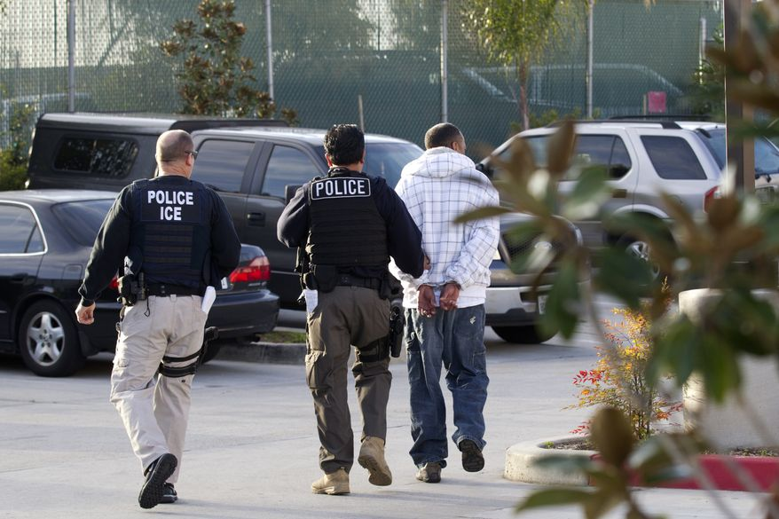 Immigration and Customs Enforcement (ICE) agents take a suspect into custody in Chula Vista, Calif., on Friday, March 30, 2012, as part of a nationwide immigration sweep. (AP Photo/Gregory Bull)