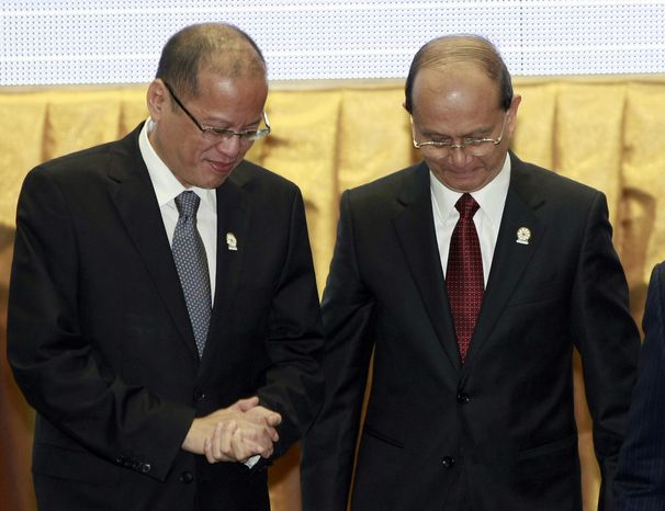 Philippine President Benigno Aquino III (left) talks with Myanmar President Thein Sein after a group photograph at the opening ceremony of the 20th ASEAN summit in Phnom Penh, Cambodia, on Tuesday, April 3, 2012. (AP Photo/Apichart Weerawong)