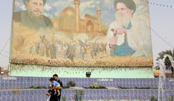 Posters of Shiite religious leaders Mohammed Sadiq al-Sadr (right) and his relative Mohammed Baqir al-Sadr (left) are on display in Baghdad's Shiite enclave of Sadr City. (AP Photo/Hadi Mizban)