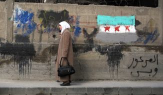 """A Syrian woman and her daughter walk April 2, 2012, past a wall with a painting of the Syrian revolutionary flag and Arabic writing that reads """"only al-Arour,"""" the name of an Islamic cleric living in Saudi Arabia who opposes President Bashar Assad, in a neighborhood of Damascus, Syria. (Associated Press)"""