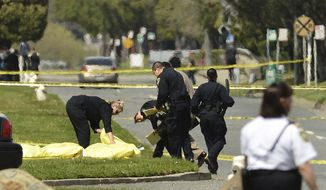 Oakland police cover bodies of shooting victims near Oikos University in Oakland, Calif., on Monday, April 2, 2012.  (AP Photo/Noah Berger)