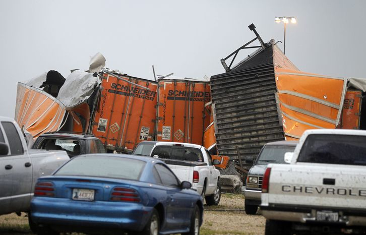 "Trailers lay smashed atop one another after a tornado reportedly tore through the southeastern portion of Dallas County, Texas, Tuesday, April 3, 2012, near Lancaster, Texas. The National Weather Service confirmed at least two separate ""large and extremely dangerous"" tornadoes in the Dallas-Fort Worth area. (AP Photo/The Dallas Morning News, G.J. McCarthy)"