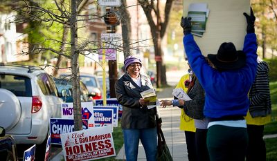 Voter Bernette Green (left) passes a gantlet of campaign volunteers as she makes her way along Alabama Avenue Southeast to cast her vote at St. Timothy's Episcopal Church in Washington as the nation's capital holds its primary election on Tuesday, April 3, 2012. (Rod Lamkey Jr./The Washington Times)