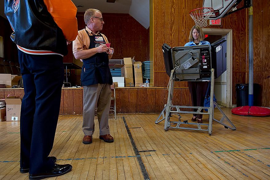 While a voter waits his turn to use the touch-screen voting machine at the Palisades Recreation Center in Washington, ballot clerk Frank Gainer (center) looks over as Cheryl Bruner votes in the D.C. primary election on Tuesday, Feb. 3, 2012. The only real contested race in this ward was for an at-large council seat. Voter turnout was not huge, but there was a steady stream of voters coming in. (Barbara L. Salisbury/The Washington Times)