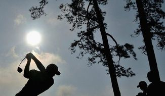 Tiger Woods, shown on the 14th hole during a practice round at Augusta, will be going for his fifth green jacket when the Masters begins Thursday. His first victory came in 1997, when he shot 18 under par. (Associated Press)