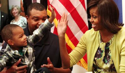 First lady Michelle Obama gets a high five from Eun White, seated with his father, Army Maj. Eunotchol White, during the first lady's visit to Fisher House at Walter Reed National Military Medical Center in Bethesda on Wednesday. (Associated Press)