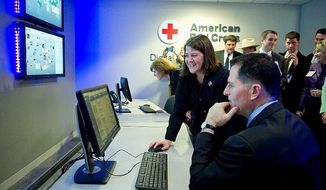 Wendy Harman of the American Red Cross shows Michael Dell of Dell Inc. the capabilities of the social media monitoring center. (Barbara L. Salisbury)