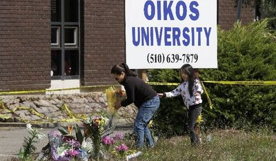Maria Campomanes and her daughter Maelauni, 9, on Wednesday leave flowers for victims of the Oikos University shooting. Ellen Cervellon, an official at the college, said she was the intended target. (Associated Press)
