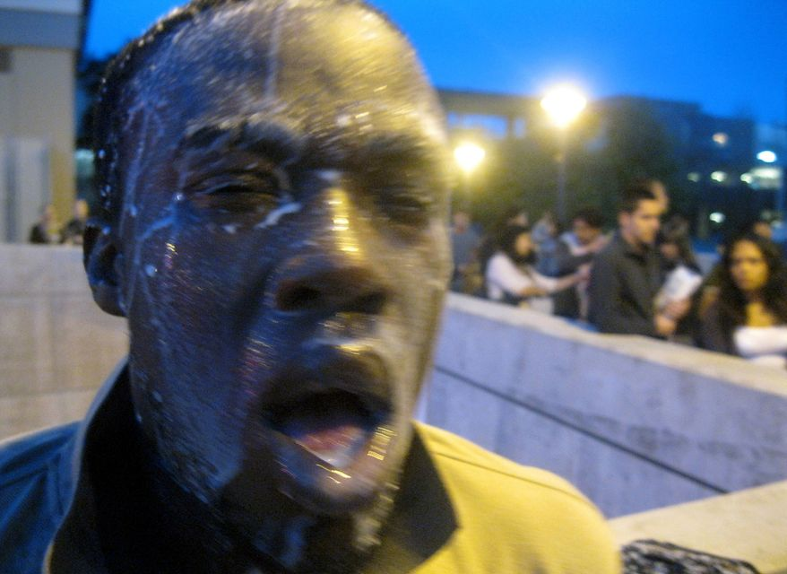 Nnaemeka Alozie, campaign manager for congressional candidate David Steinman, reacts with milk on his face after being pepper-sprayed during a protest on April 3, 2012, at Santa Monica College in Santa Monica, Calif. Campus police pepper-sprayed as many as 30 demonstrators after students angry over a plan to offer high-priced courses tried to push their way into a trustees meeting, authorities said. (Associated Press/Courtesy of David Steinman)